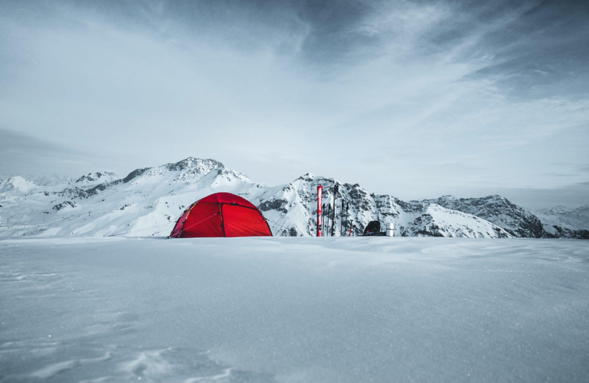 Rotes Zelt im Winter auf Skitour, Wintercamping